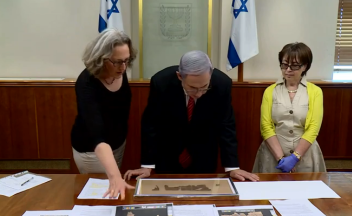Prime Minister Benjamin Netanyahu (center) views a 2,000-year-old Book of Lamentations scroll on Tisha B'Av. Credit: GPO.