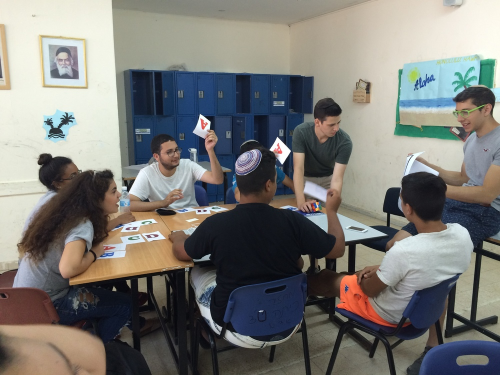 Click photo to download. Caption:Zach Katz(second from right, standing)of Bergenfield, N.J., and Elan Rotenberg(far right)of Baltimore, Md., run an English class for Counterpoint Israel campers in Kiryat Gat. Credit: CourtesyCounterpoint Israel.
