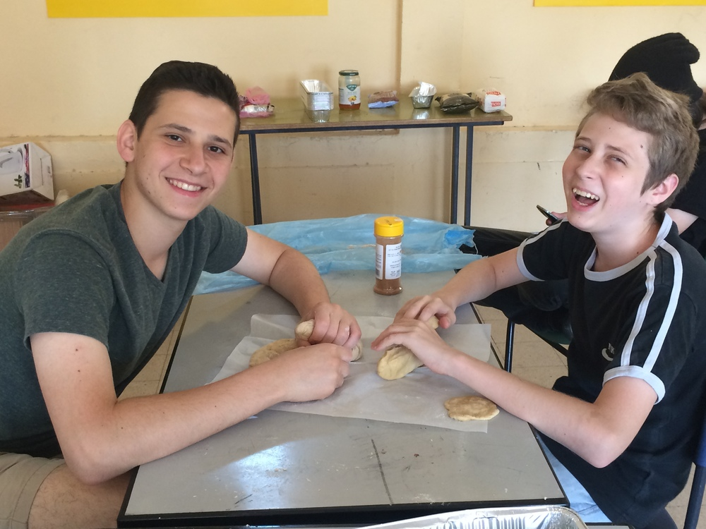 Click photo to download. Caption: Zach Katz (left) of Bergenfield, N.J., prepares challah with a happy camper in Kiryat Gat. Credit: Courtesy Counterpoint Israel.