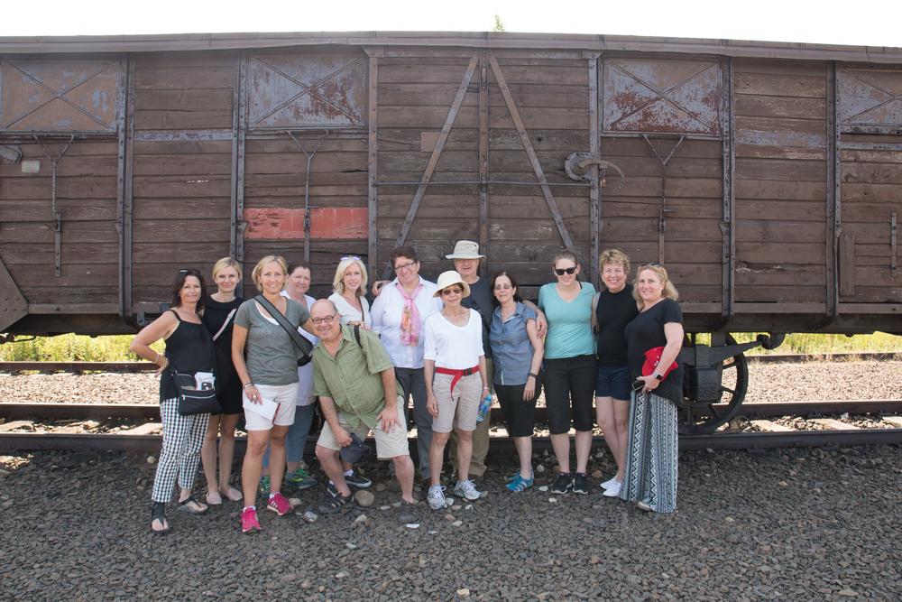 Click photo to download. Caption: Participants of the July 2015 European Holocaust tour of the Alfred Lerner Fellowship for Holocaust educators pose in front of a railcar outside of the Auschwitz-Birkenau concentration camp. Credit: Pawel Sawicki.