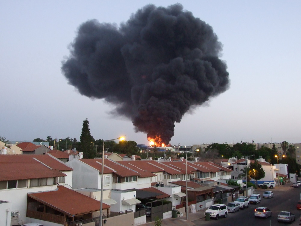 Click photo to download. Caption: A factory in the southern Israeli city of Sderot bursts into flames after being hit by a rocket from Gaza during last summer's Hamas-Israel conflict. Credit: Natan Flayer via Wikimedia Commons.