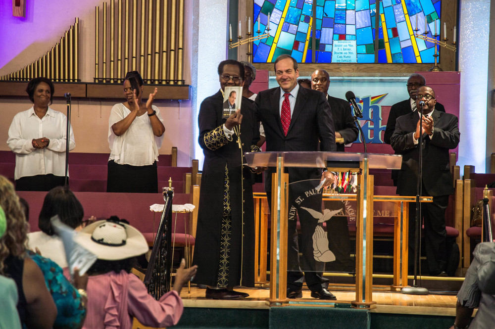 "Click photo to download. Caption: On Aug. 16 in Detroit, Rabbi Yechiel Eckstein (center right, at podium), founder and president of the International Fellowship of Christians and Jews, with New St. Paul Tabernacle Church of God in Christ Bishop P.A. Brooks, who is holding a copy of ""The Bridge Builder,"" the new biography of Eckstein. Credit: Justin McMahan."