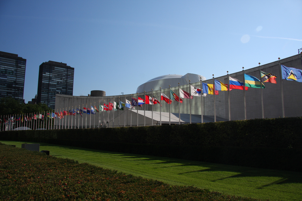The row of flags of United Nations member countries in front of the U.N. General Assembly building in New York City. Credit: Yerpo via Wikimedia Commons.