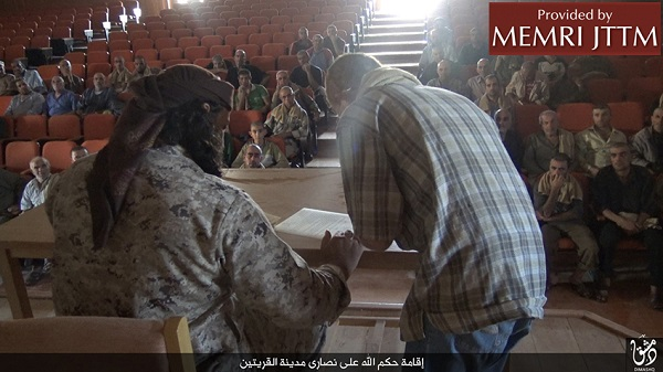 "An Islamic State terrorist (left) presides over a Syrian Christian's signing of a ""dhimmi"" contract. Credit: MEMRI."