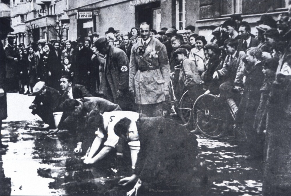 Click photo to download. Caption: Jews being forced to scrub the streets in Vienna in 1938. Credit: Courtesy of The David S. Wyman Institute for Holocaust Studies.