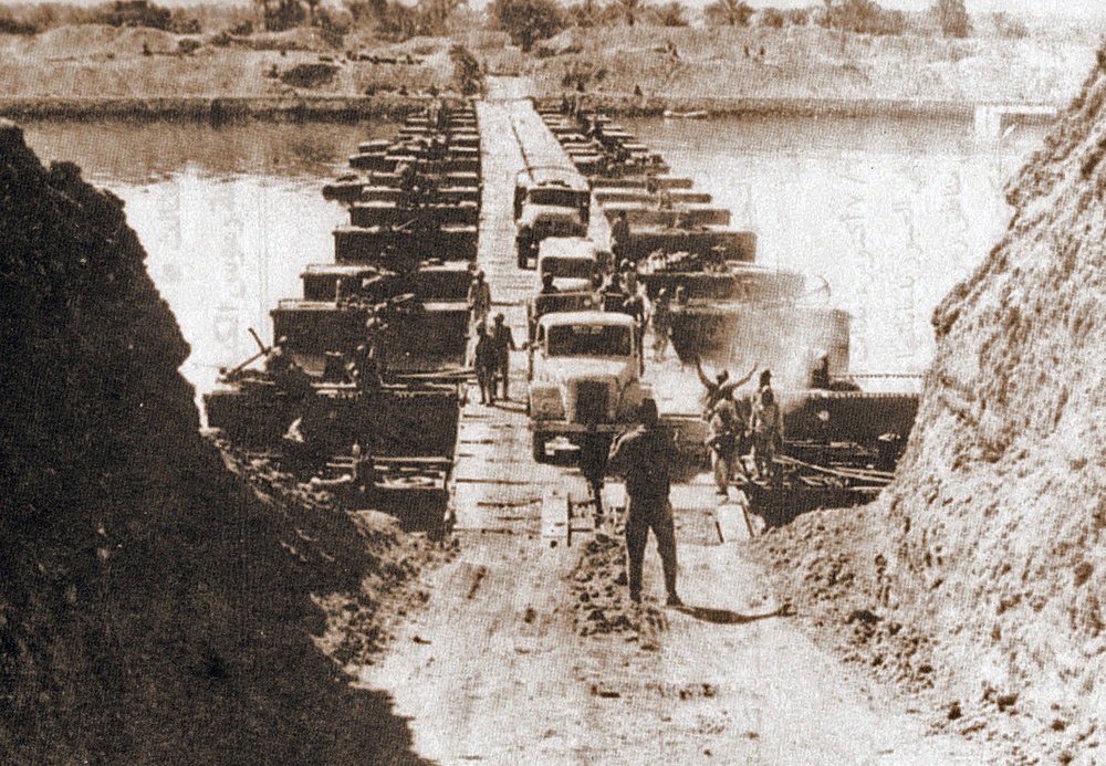 Egyptian military trucks cross a bridge laid over the Suez Canal on October 7, 1973, during the Yom Kippur War. Credit: Wikimedia Commons.