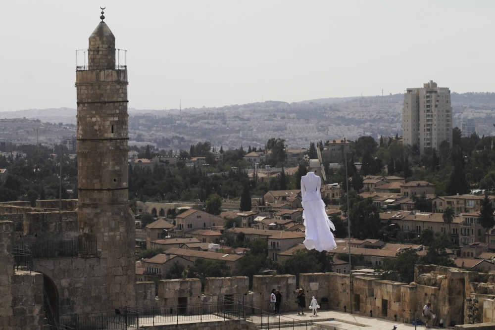 """Click photo to download. Caption: A white bridal dress floats in the air near the Tower of David as part of the 2nd Jerusalem Biennale's installation called """"Betrothal.""""Credit: Ricky Rachman."""
