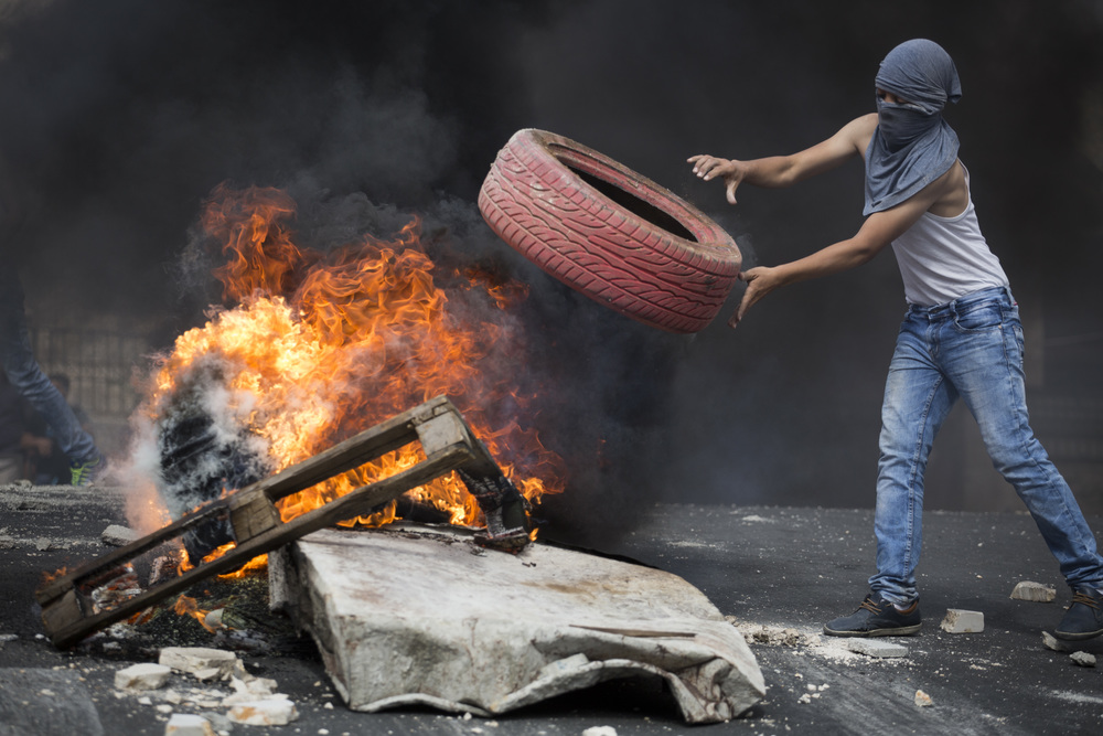 Click photo to download. Caption: On Oct. 7, 2015, a Palestinian rioter throws a tire into a fire, blocking a road during clashes with Israeli police in eastern Jerusalem. Credit: Hadas Parush/Flash90.