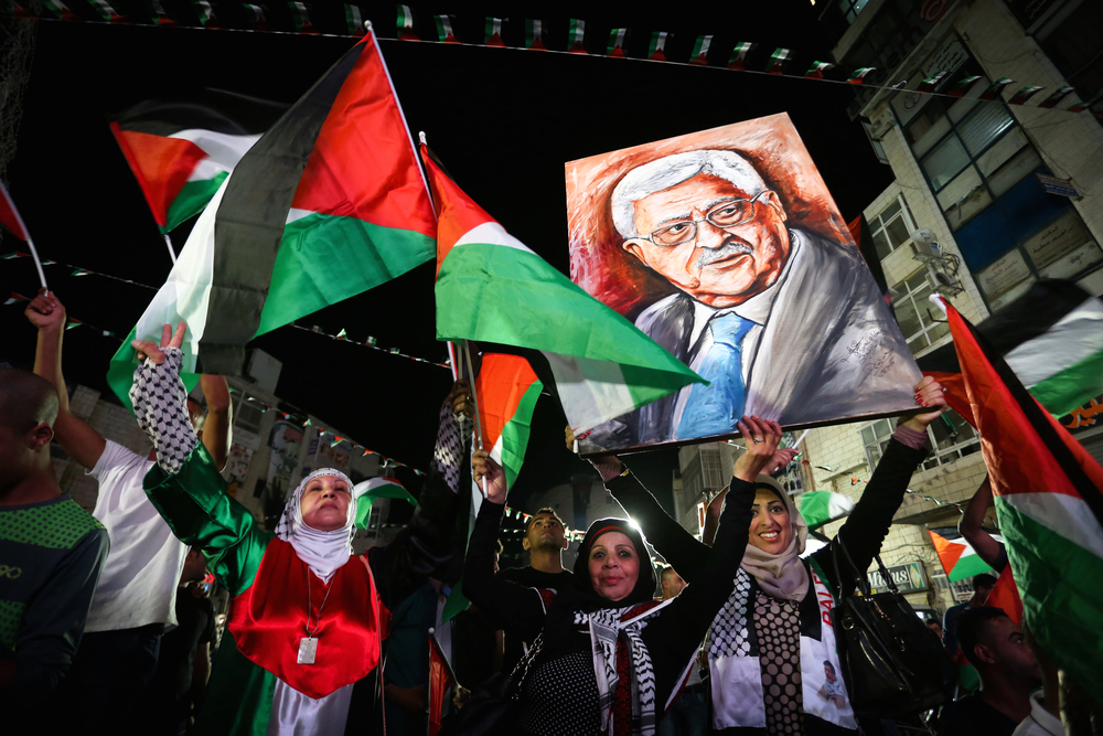 Click photo to download. Caption: Palestinians in Ramallah wave their national flags and a picture of Palestinian Authority President Mahmud Abbas while they watch a live-screening of Abbas's United Nations speech on Sept. 30, 2015. Credit: Flash90.