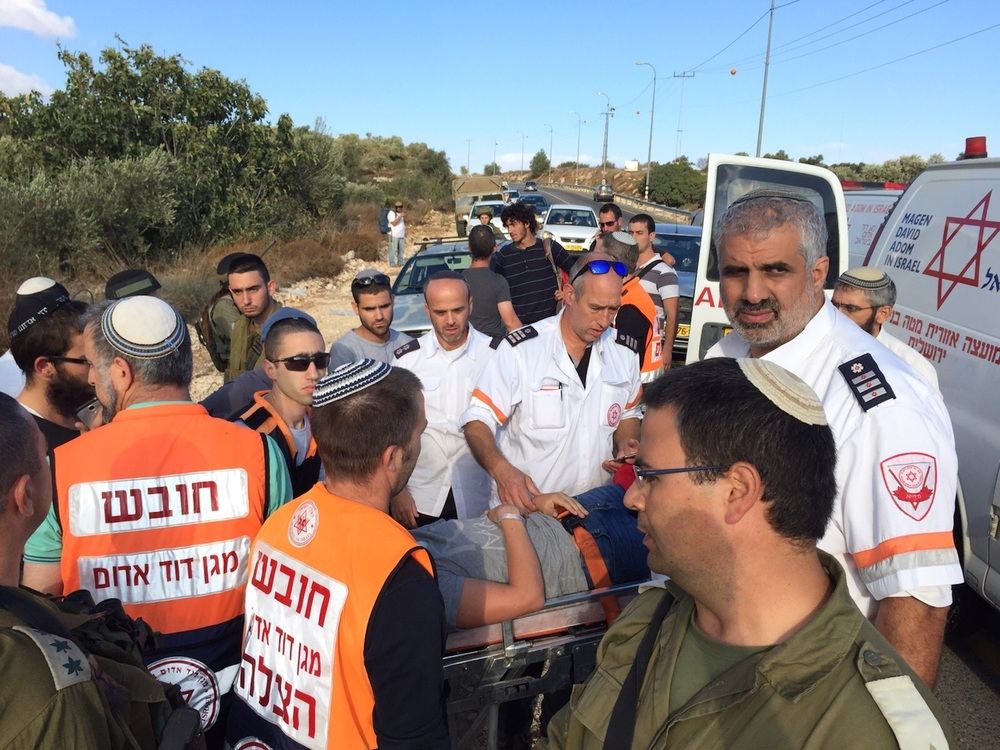 Click photo to download. Caption: Israeli Magen David Adom (MDA) paramedics provide medical treatment to four adults and two children after stones were thrown at their car on Oct. 9. Credit: MDA.
