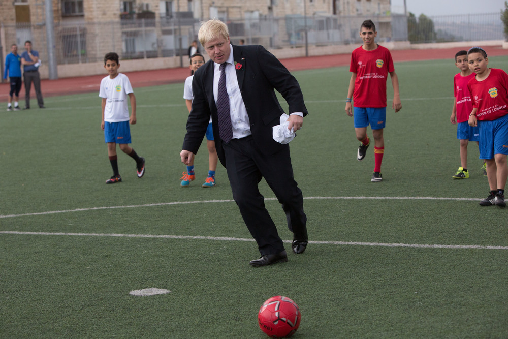 "Click photo to download. Caption: London Mayor Boris Johnson plays soccer with Jewish and Arab youths as part of the ""Equalizer"" coexistence project in Jerusalem on Nov. 10, 2015. Credit: Yonatan Sindel/Flash90."