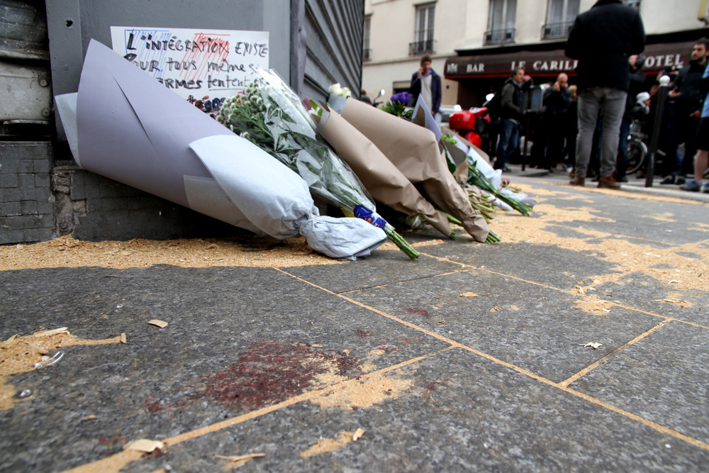 Click photo to download. Caption: The Le Petit Cambodge restaurant—site of one of six coordinated Islamist terror attacks in Paris on Friday—with a makeshift memorial of flowers and blood staining the ground on the day after the attacks. Credit: Maya-Anaïs Yataghène via Wikimedia Commons.