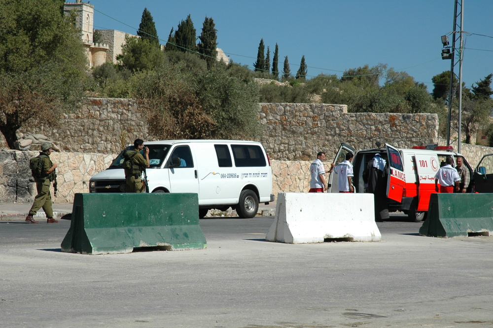 At right, a Palestinian Red Crescent ambulance. Credit: Justin McIntosh via Wikimedia Commons.