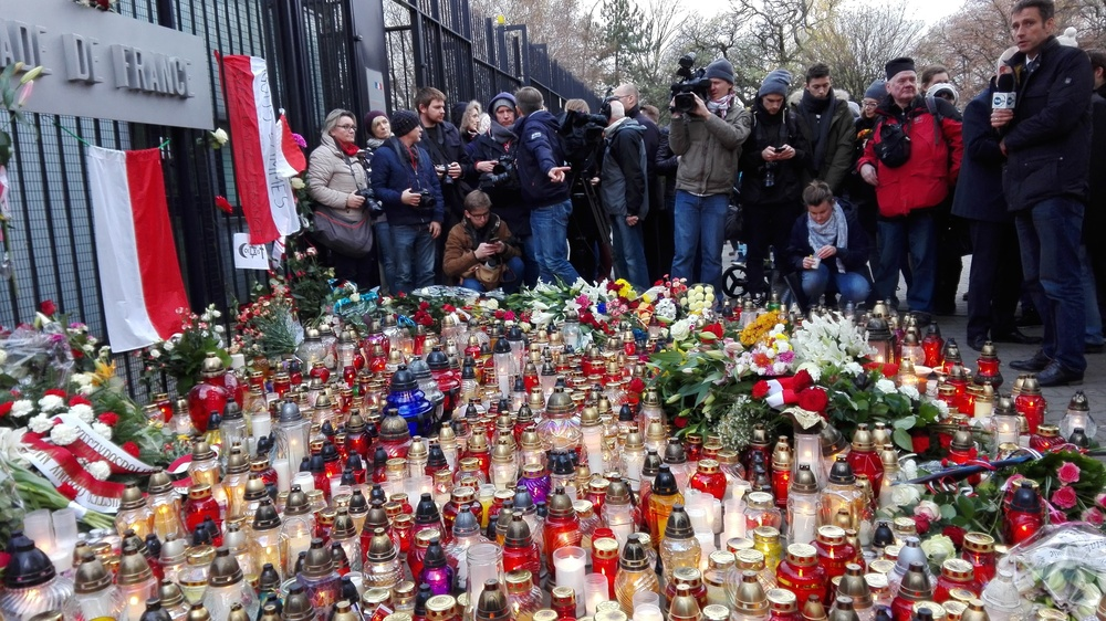 Click photo to download. Caption: Candles and flowers for the victims of the Nov. 13 Paris attacks outside of the French Embassy in Warsaw. Credit: Halibutt via Wikimedia Commons.