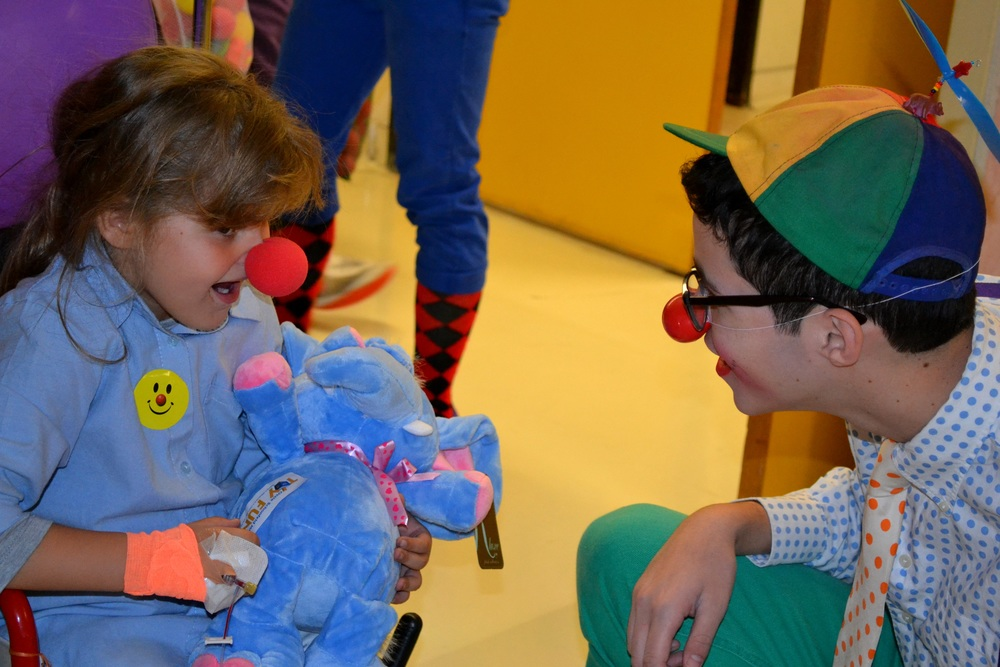 Click photo to download. Caption: A Lev Leytzan medical clown (at right) with a child patient. Credit: Courtesy Lev Leytzan.