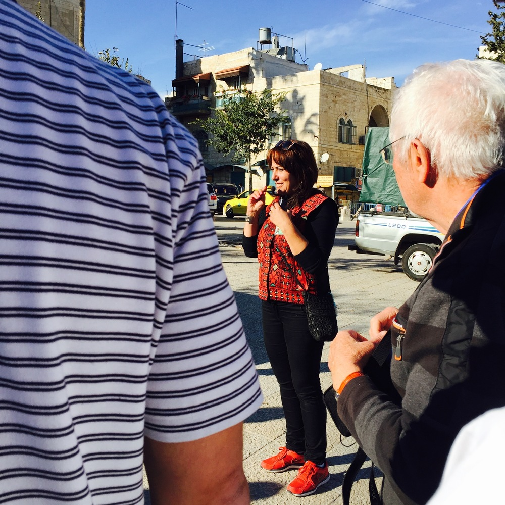 Click photo to download. Caption: Khadra Zreineh provides a tour of the Church of the Nativity to a group from Germany. Credit: Maayan Jaffe.