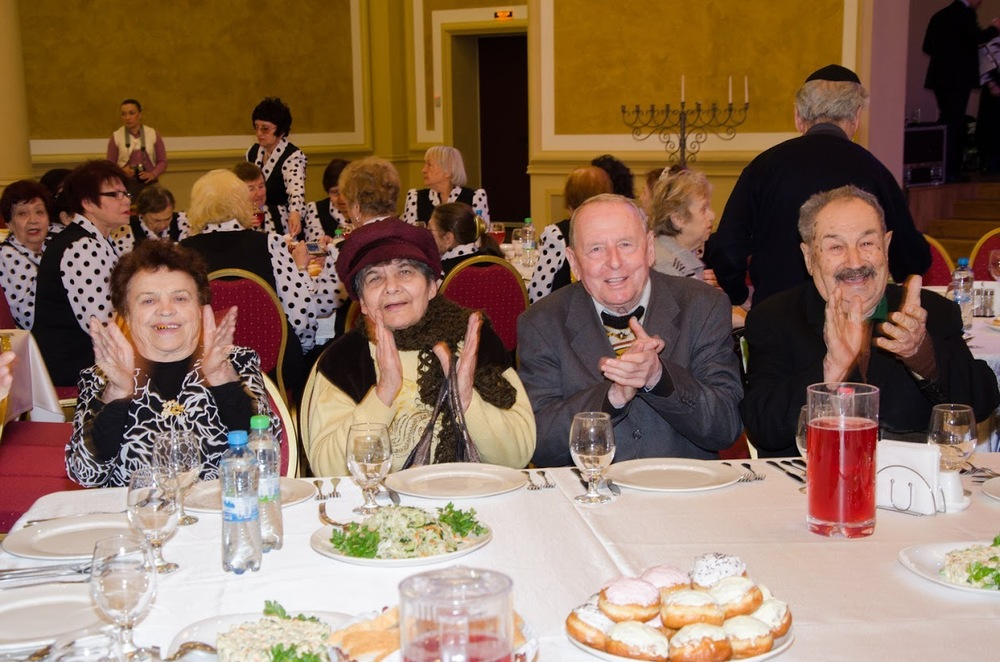Click photo to download. Caption: Elderly Hesed social welfare center clients celebrate Hanukkah at a traditional meal in Dnepropetrovsk, Ukraine. Credit: JDC.