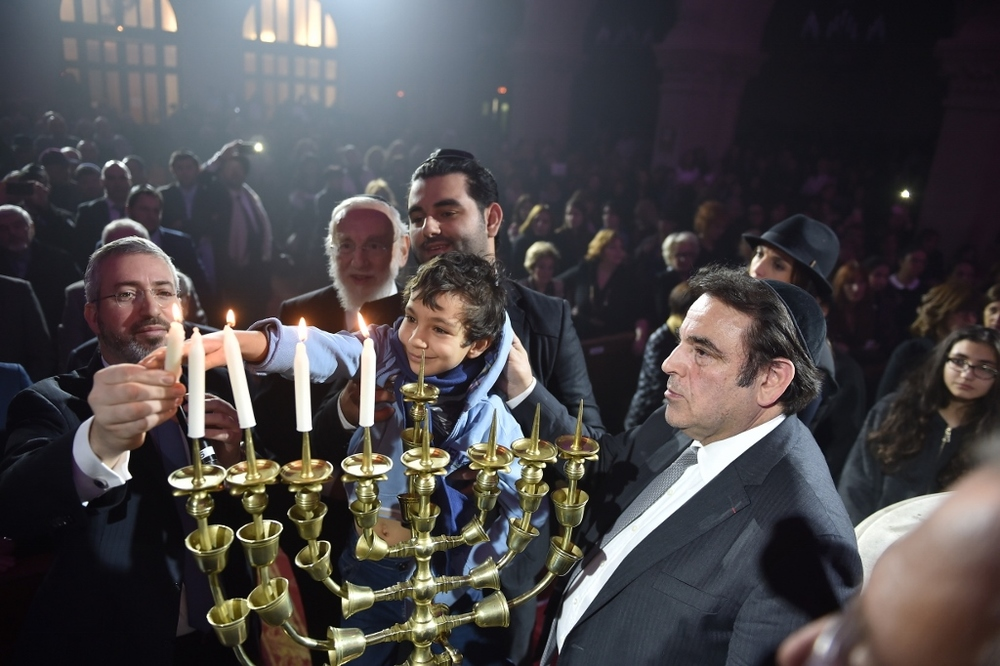 "Click photo to download. Caption: Relatives of the Hyper Cacher terrorist attack victims (Philippe Braham, Yohan Cohen, Yoav Hattab, and François-Michel Saada) light Hanukkah candles at this week's ""Let There Be Light: A Concert of Jewish Unity"" at Grande Synagogue de la Victoire – the Great Synagogue of Paris. Credit: Israel Bardugo."