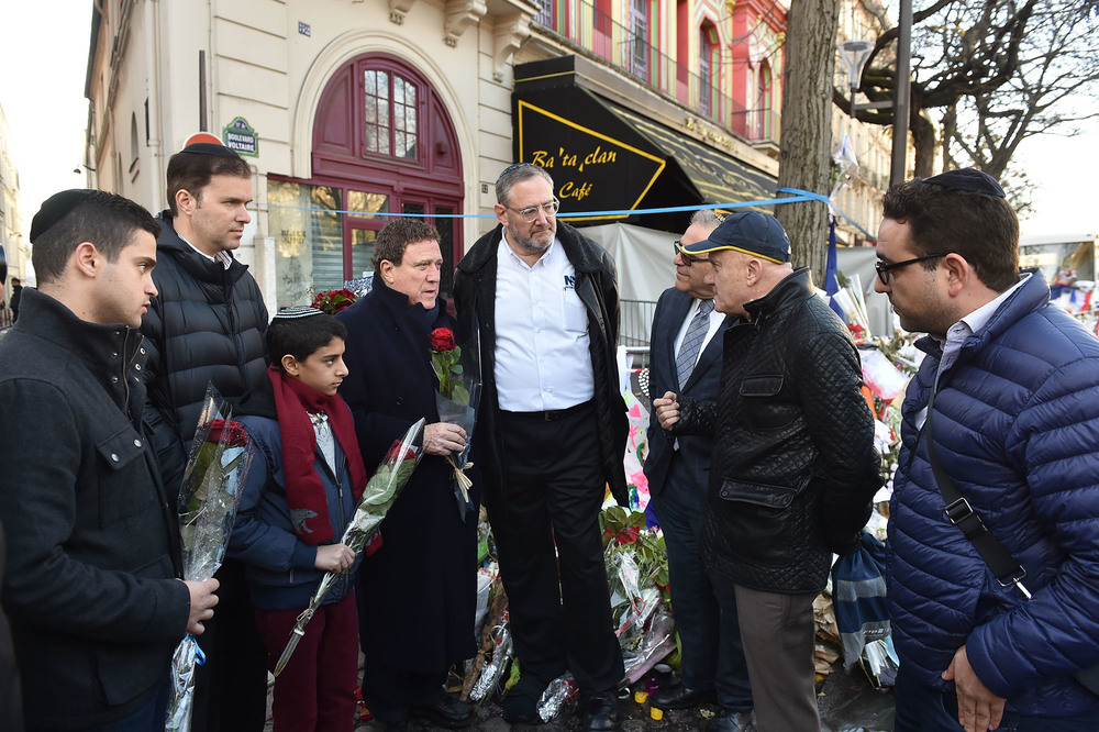 Click photo to download. Caption: From left to right—Itzik Dadya, Ohad Moskowitz, Ouzia Tzadok, Yehoram Gaon, Nachum Segal, Richard Joel, and Robert Benrimon outside the Bataclan theater in Paris, site of one of six coordinated Islamist terror attacks last month. Credit: Israel Bardugo.