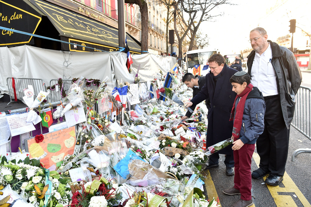 Click photo to download. Caption: Nachum Segal looks on as Yehoram Gaon and Ouzia Tzadok lay flowers outside the Bataclan theater in Paris, site of one of six coordinated Islamist terror attacks last month. Credit: Israel Bardugo.