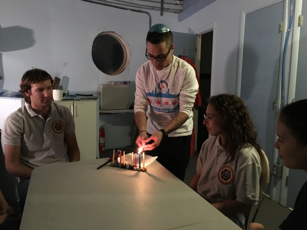 Click photo to download. Caption: Barak Stoltz lights Hanukkah candles in the Mars Desert Research Station. Credit: Courtesy Barak Stoltz.