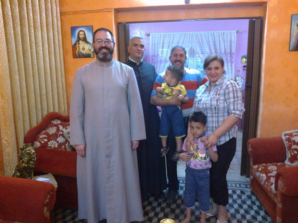 Father Luis Montes with a Iraqi Christian family. Credit: Friends of Iraq.