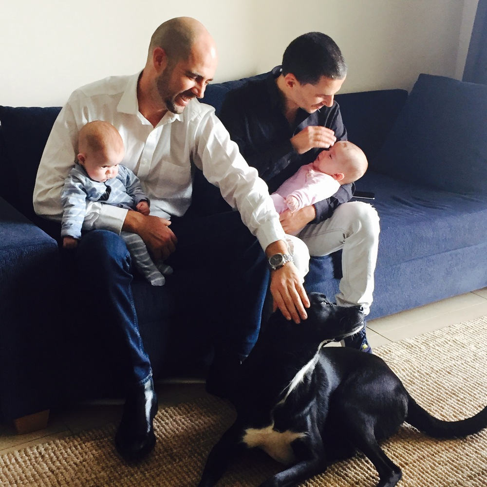 Click photo to download. Caption: Member of Knesset Amir Ohana (left) and his partner Alon Hadad are pictured with their 4-and-a-half-month-old twins, Elah and David, and their dog, Guri. Credit: Maayan Jaffe.
