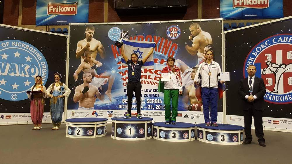 Click photo to download. Caption: Nili Block (in center) raises her arms and trophy in victory at the October 2015 Kickboxing World Championships in Belgrade, Serbia. Credit: Courtesy Nili Block.