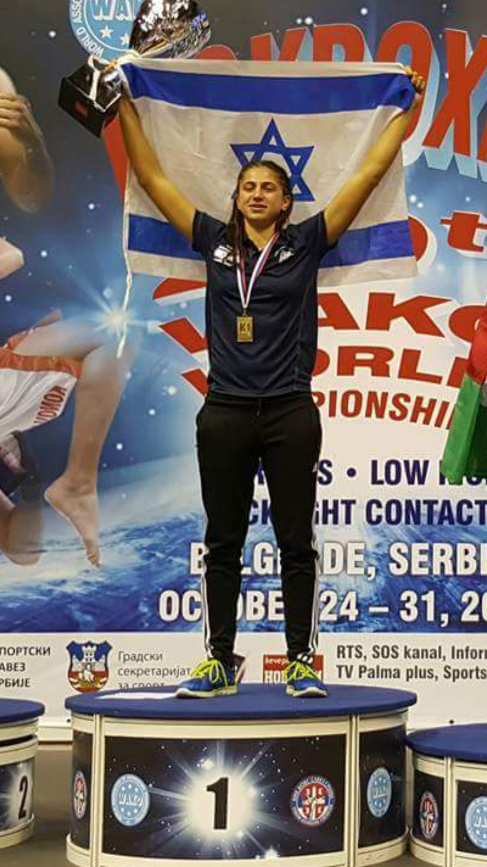 Click photo to download. Caption: Nili Block raises her arms and trophy in victory at the October 2015 Kickboxing World Championships in Belgrade, Serbia. Credit: Courtesy Nili Block.