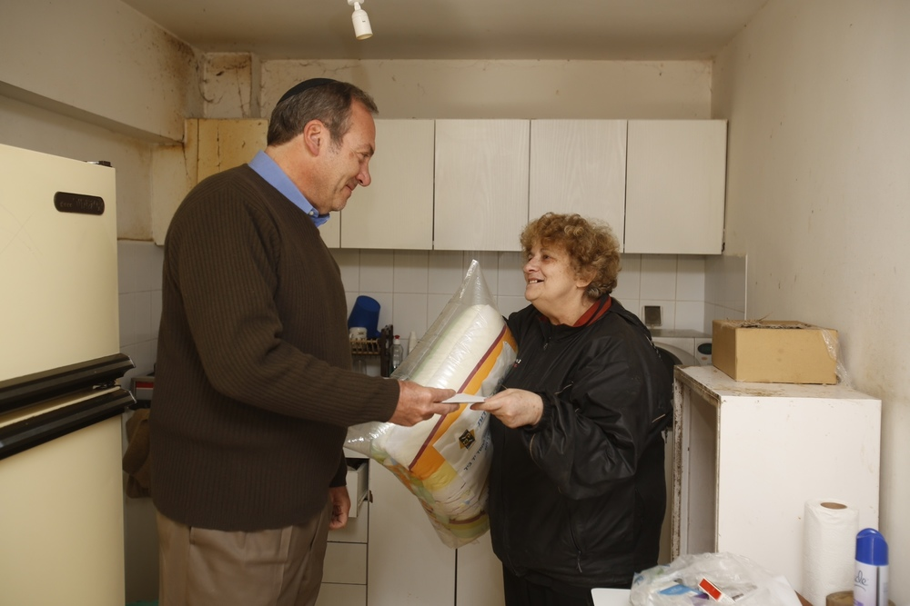 Click photo to download. Caption: In Israel, Rabbi Yechiel Eckstein (left) meets with Olga, an immigrant from the former Soviet Union and a recipient of aid from a food program of the Eckstein-led International Fellowship of Christians and Jews. Credit: Courtesy International Fellowship of Christians and Jews.