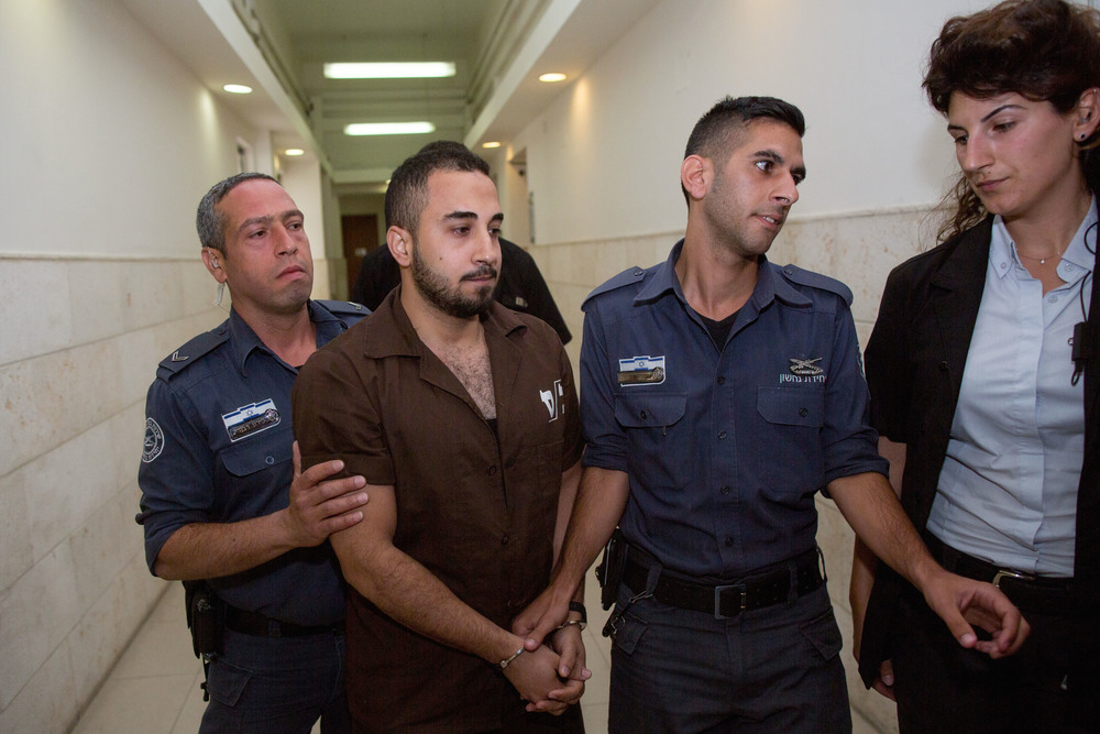 Click photo to download. Caption: Khalil Adel Khalil (second from left), 25, of the A-Tur neighborhood in Jerusalem, is brought to Jerusalem's District Court on July 9, 2015. Khalil, who admitted to trying to join the Islamic State terror group in Syria, was sentenced to two years in prison. Credit: Yonatan Sindel/Flash90.