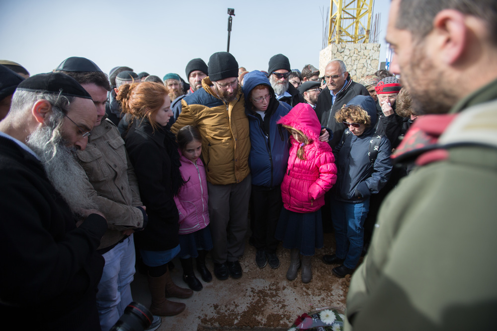 Click photo to download. Caption: In center, the husband and children of Israeli victim of terror Dafna Meir look down at her fresh grave during her funeral in Jerusalem on Jan. 18. Credit: Yonatan Sindel/Flash90.
