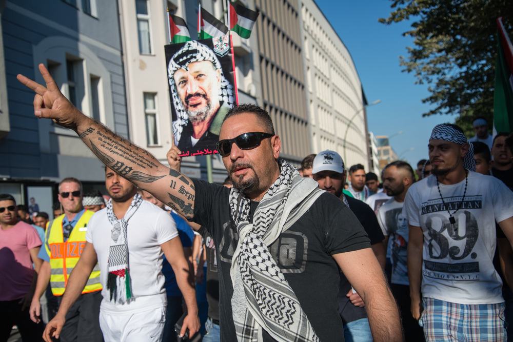 "Click photo to download. Caption: In July 2014 in Berlin, Germany, demonstrators carry a picture of late Palestinian leader Yasser Arafat and protest against the Israeli military's Operation Protective Edge in Gaza. Berlin-based scholar Benjamin Weinthal tells JNS.org that Germany, despite overcoming its Holocaust past, has ""failed to internalize that modern anti-Semitism—hatred of the Jewish state and the delegitimization of Israel via product labels, for example—is the main problem."" Credit: Boris Niehaus via Wikimedia Commons."