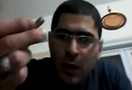 Arab Terrorist Nashat Milhem holds a bullet in a video recovered from his cell phone. Credit: Screenshot via Shin Bet.