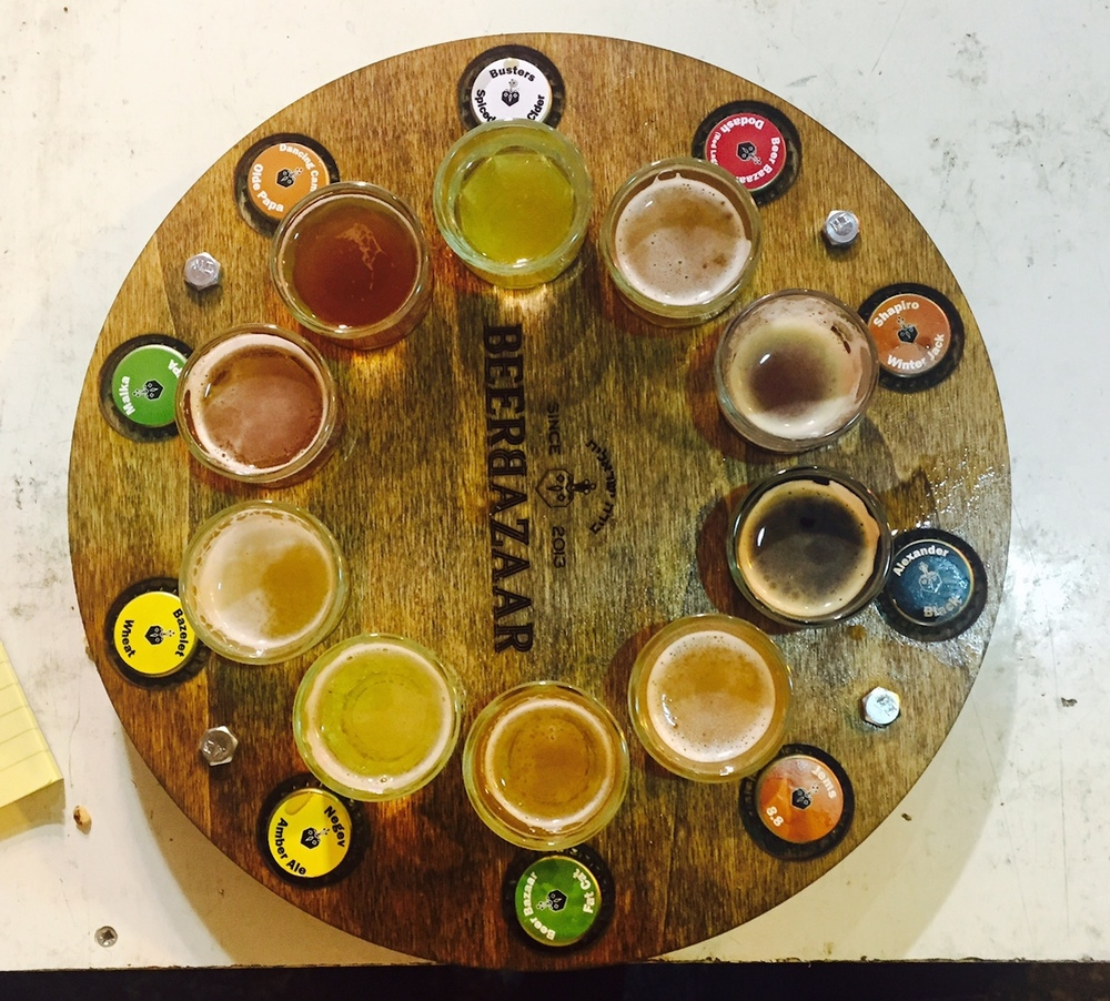Click photo to download. Caption: The tap wheel, giving customers a shot each of 10 beers, at the Beer Bazaar in Jerusalem's Shuk Mahane Yehuda. Credit: Maayan Jaffe.