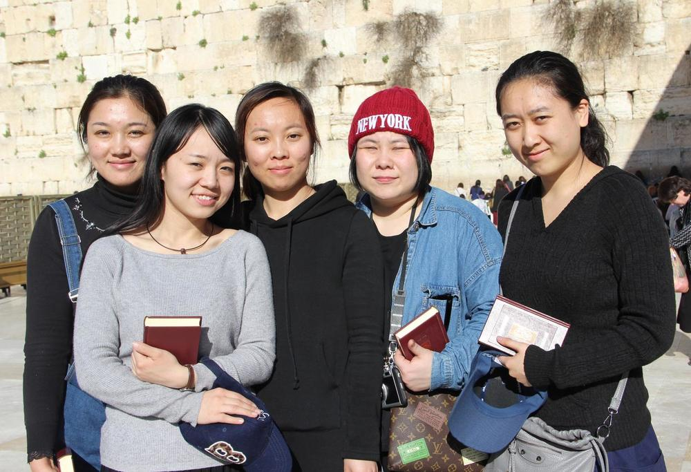 Caption: From left to right, five new Chinese immigrants to Israel—Li Yuan, Yue Ting, Li Jing, Li Chengjin, and Gao Yichen—stand in front of the Western Wall. Credit: Laura Ben-David/Courtesy of Shavei Israel.