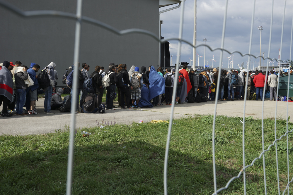 Click photo to download. Caption: Syrian refugees wait in line to cross the border of Hungary and Austria on their way to Germany in September 2015. Credit: Mstyslav Chernov via Wikimedia Commons.