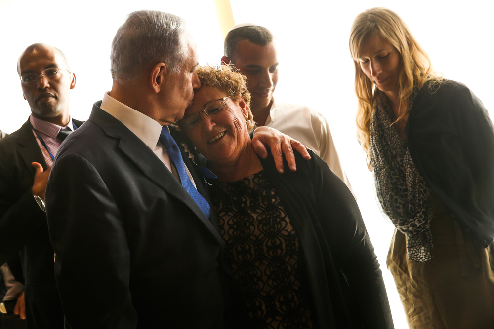 Click photo to download. Caption: Israeli Prime Minister Benjamin Netanyahu (at left in front) kisses Miriam Peretz, mother of fallen Israeli soldiers Uriel and Eliraz Peretz, during the opening session of the 20th Israeli Knesset on March 31, 2015. Credit: Nati Shohat/Flash90.