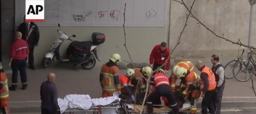 Emergency responders caring for a wounded person at the scene of the train station blast in Brussels on Tuesday. Credit: Screenshot from YouTube.