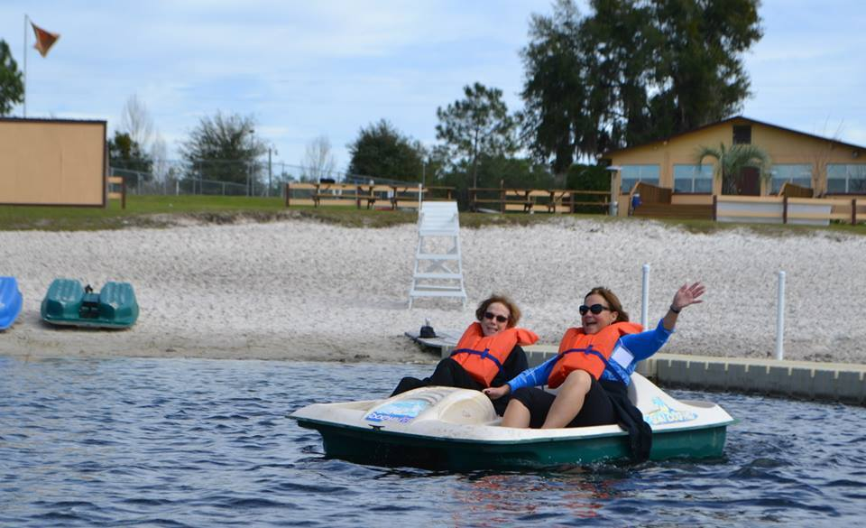 Click photo to download. Caption: Grown-up campers ride a paddleboat at central Florida's Camp Shalom. Credit: Camp Shalom.