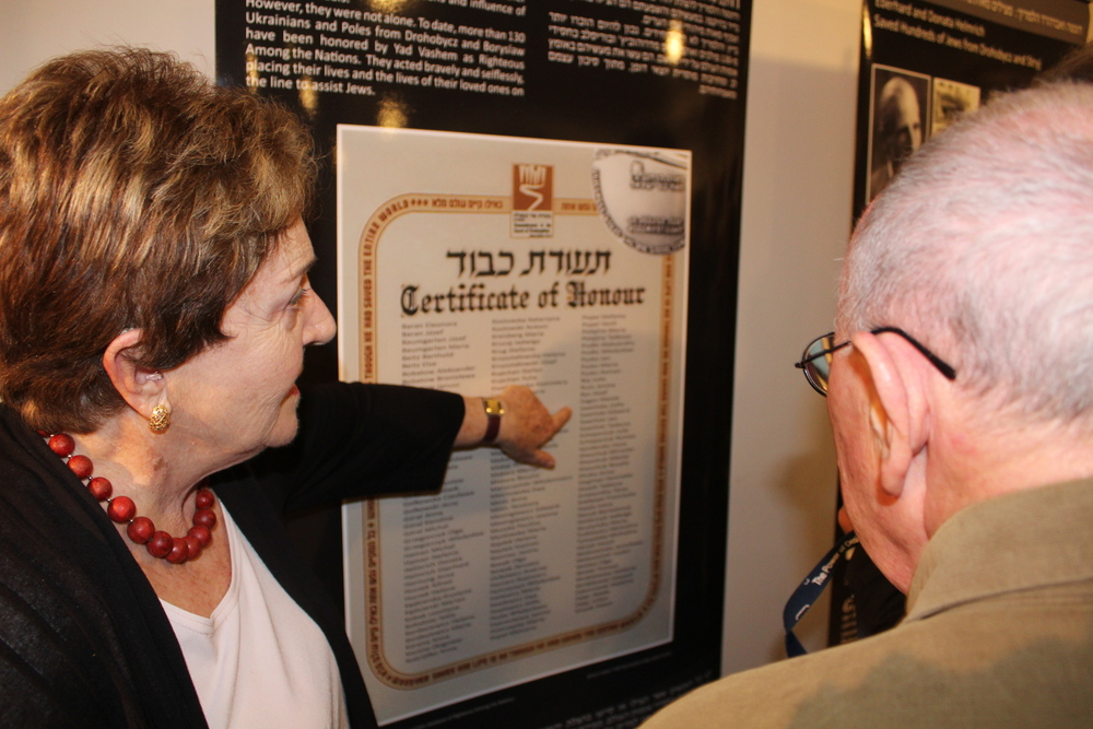 "Click photo to download. Caption: Standing in front of a poster at the Tel Aviv's Beit Hatfutsot museum with a list of individuals who had saved Jews in Drohobych-Boryslav during the Holocaust, Irena Wysoki points to the names ""Jan Sawiński"" and ""Zofia Sawińska,"" Polish farmers who hid Wysoki and her brother. Credit: Eitan Arom."