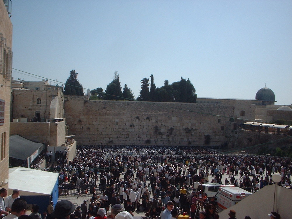 Click photo to download. Caption: A large crowd gathers at the Western Wall on Passover to receive the priestly blessing, known as birkat kohanim. Credit: Wikimedia Commons.