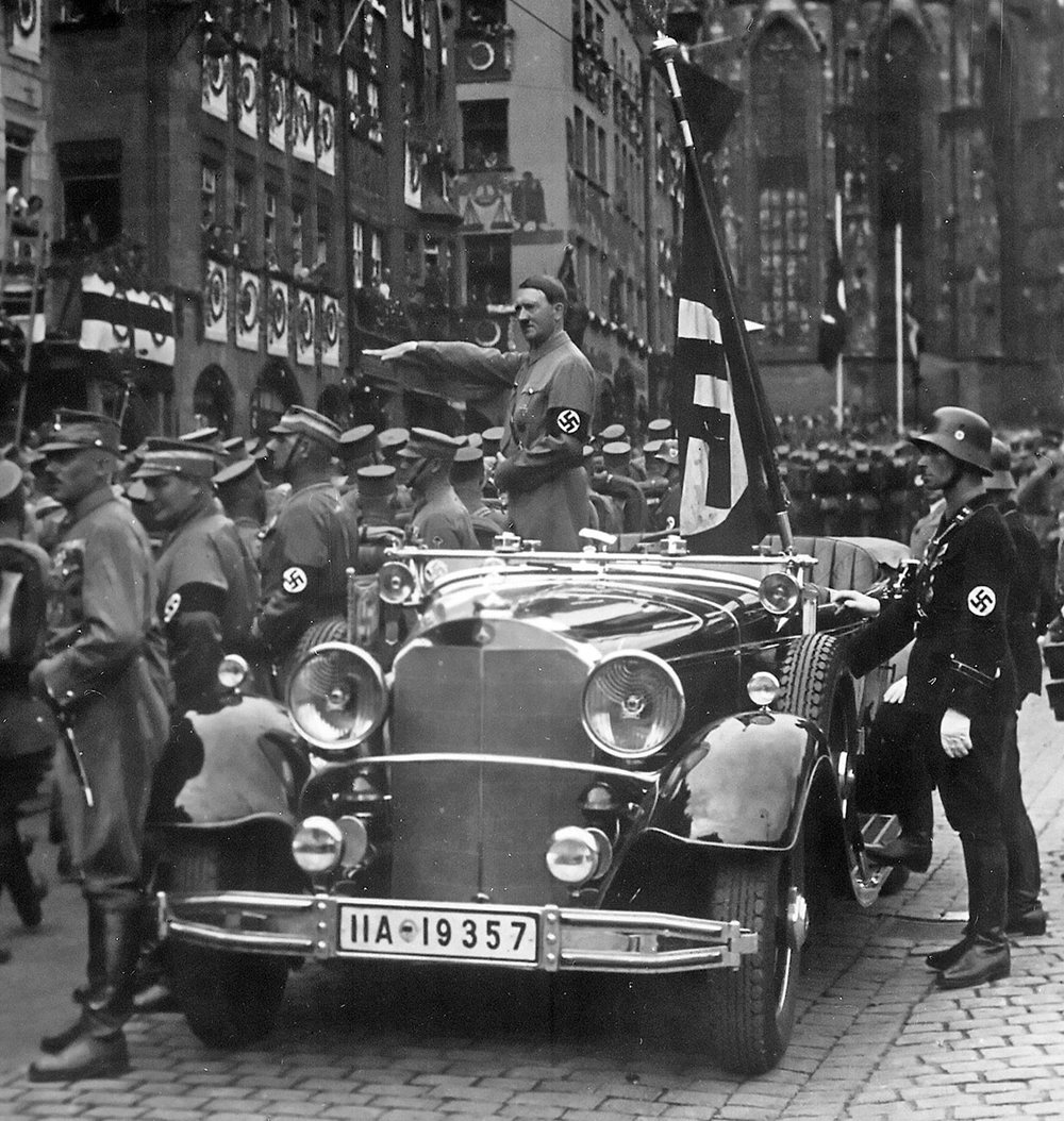 A parade of SA troops passes Hitler in Nuremberg, Germany. Credit: Charles Russell Collection, NARA via Wikimedia Commons.