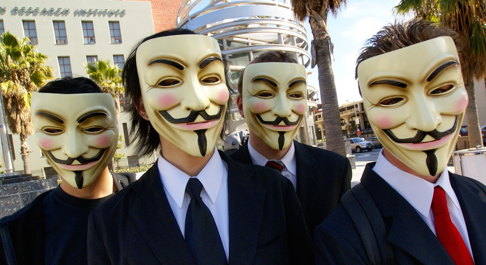 Click photo to download. Caption: In Los Angeles, four people appear in public as members of the global hacking network known as Anonymous. Credit: Vincent Diamante via Wikimedia Commons.