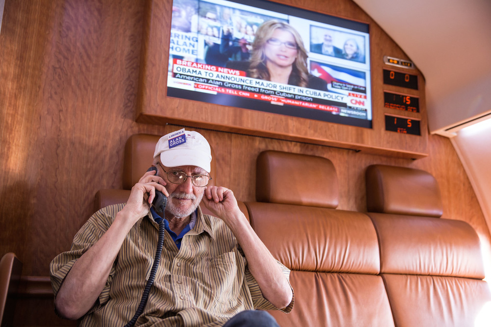 Click photo to download. Caption: Alan Gross speaks over the phone with President Barack Obama onboard a government plane headed from Cuba to the U.S. on Dec. 17, 2014, the day Gross was released from Cuban prison. Credit: Lawrence Jackson/White House.