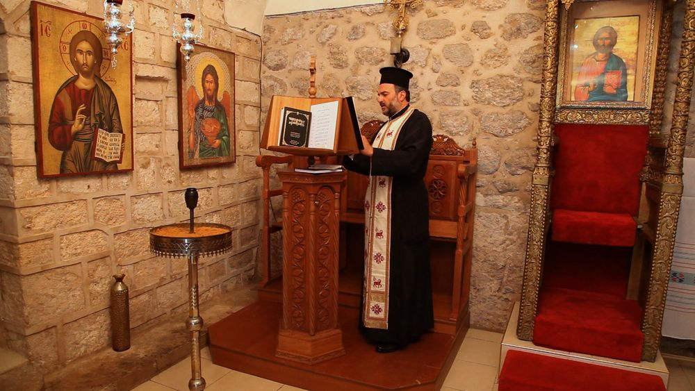 "Click photo to download. Caption: Father Gabriel Naddaf, a Greek Orthodox priest who promotes Arab-Christian integration into Israeli society, in a scene from ""My Home."" Credit: My Home."
