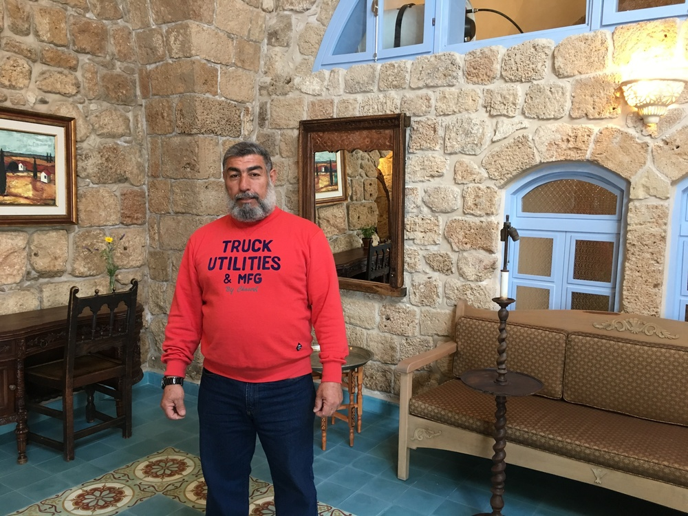 "Click photo to download. Muhammad Abu Marwan in a guest room in Akko's ""Arabesque: An Arts and Residency Center."" Credit: Orit Arfa."