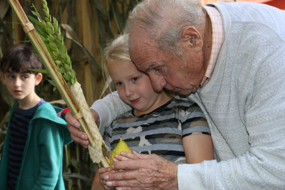 Click photo to download. Caption: A resident of the NewBridge on the Charles retirement community in Dedham, Mass., helps a 2nd-grade student at The Rashi School shake the Four Species of Sukkot. Credit: Courtesy Hebrew SeniorLife.