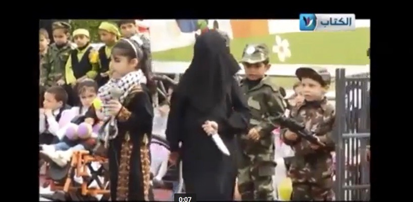A Palestinian child is seen brandishing a fake knife in a simulated terror attack against Israelis. Credit: YouTube screenshot.