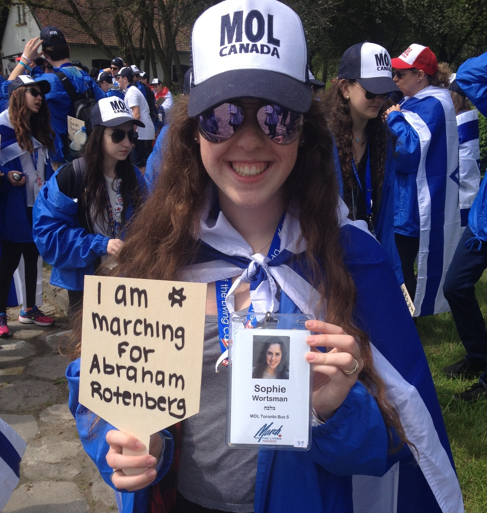 Click photo to download. Caption: Sophie Worstman of Toronto holds a sign bearing the name of her great uncle, Holocaust victim Abraham Rotenberg, before taking part in the 2016 March of the Living from Auschwitz to Birkenau. Credit: Jacob Kamaras.